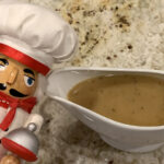 Tan gravy in a white gravy boat. There's a nutcracker who looks like a chef in the foreground.
