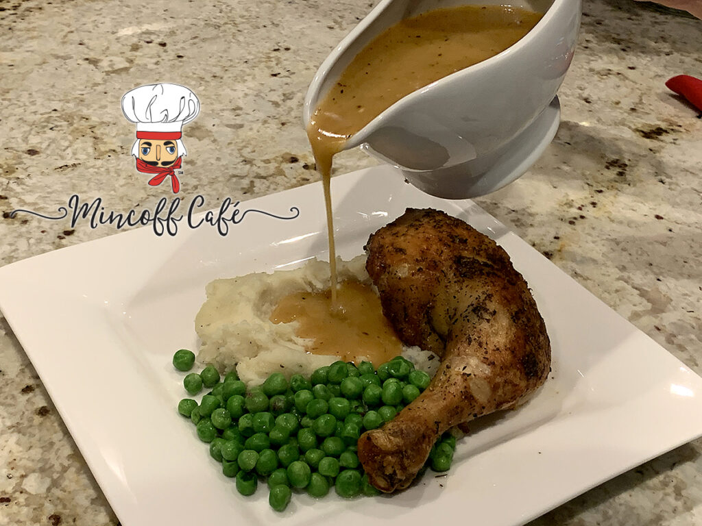 Square white plate with Chicken leg quarter, peas and mashed potatoes. Gravy is being poured out of a white dish onto the mashed potatoes.
