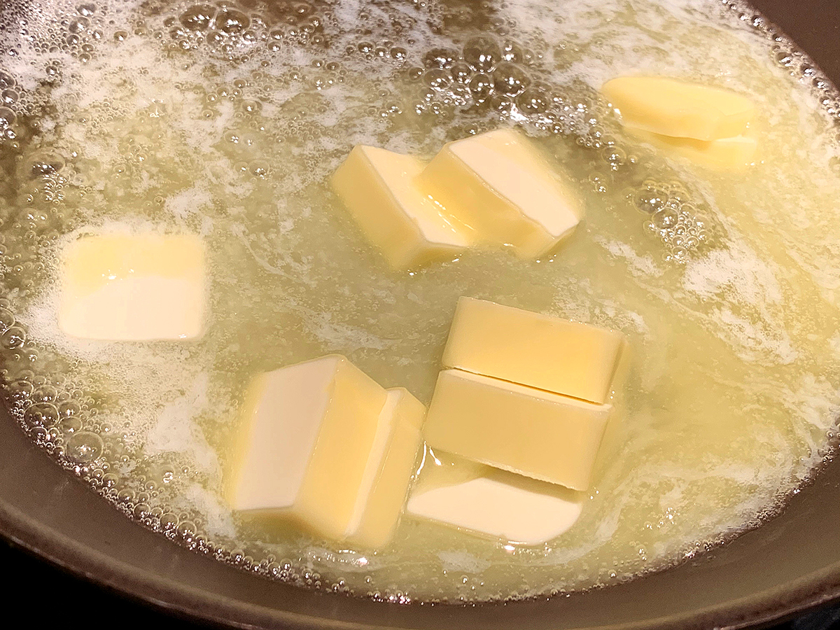Cubes of butter melting in a small skillet.