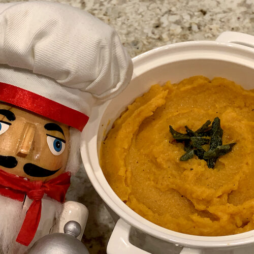 Amber mashed butternut squash in a round white bowl with some fried sage on top. There's a nutcracker who looks like a chef in the foreground.
