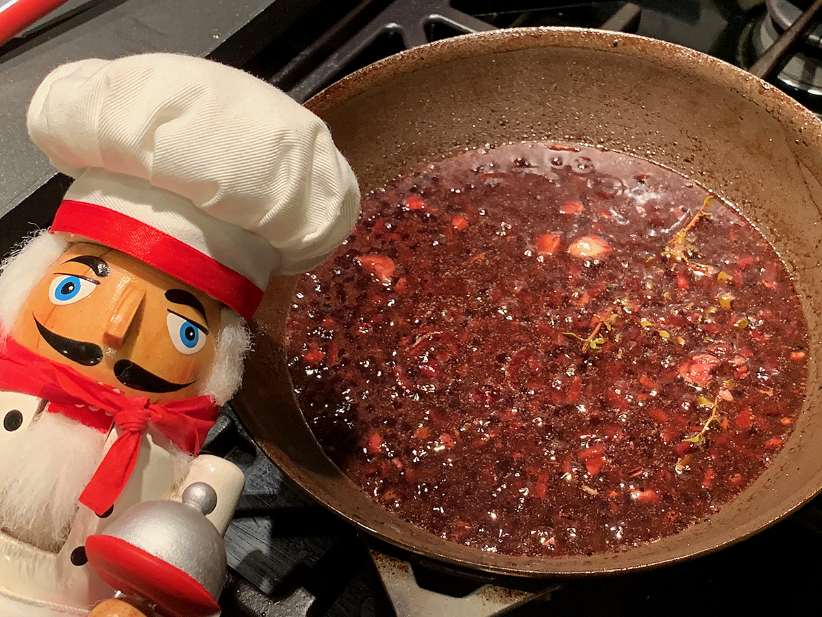 Pomegranate wine sauce in a small skillet. There's also a nutcracker in the foreground who looks like a chef.