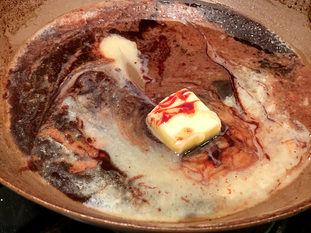 Square piece of butter melting in a pan with pomegranate wine sauce.