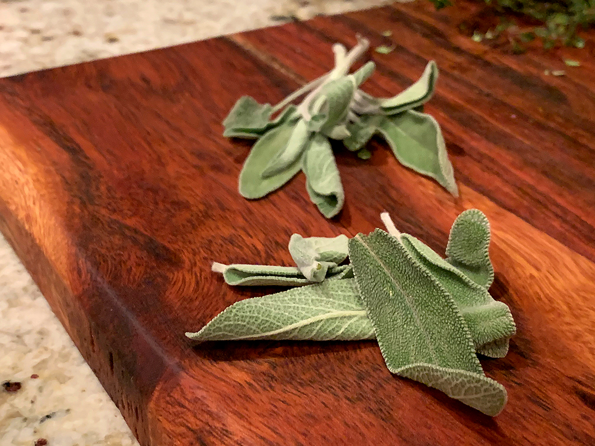 Fresh sage leaves on a wood cutting board.