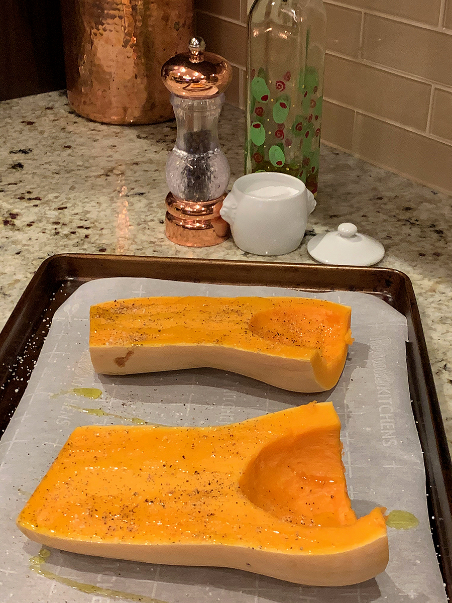 Two halves of a butternut squash, face up on a parchment lined sheet pan, seasoned with olive oil, salt and pepper.