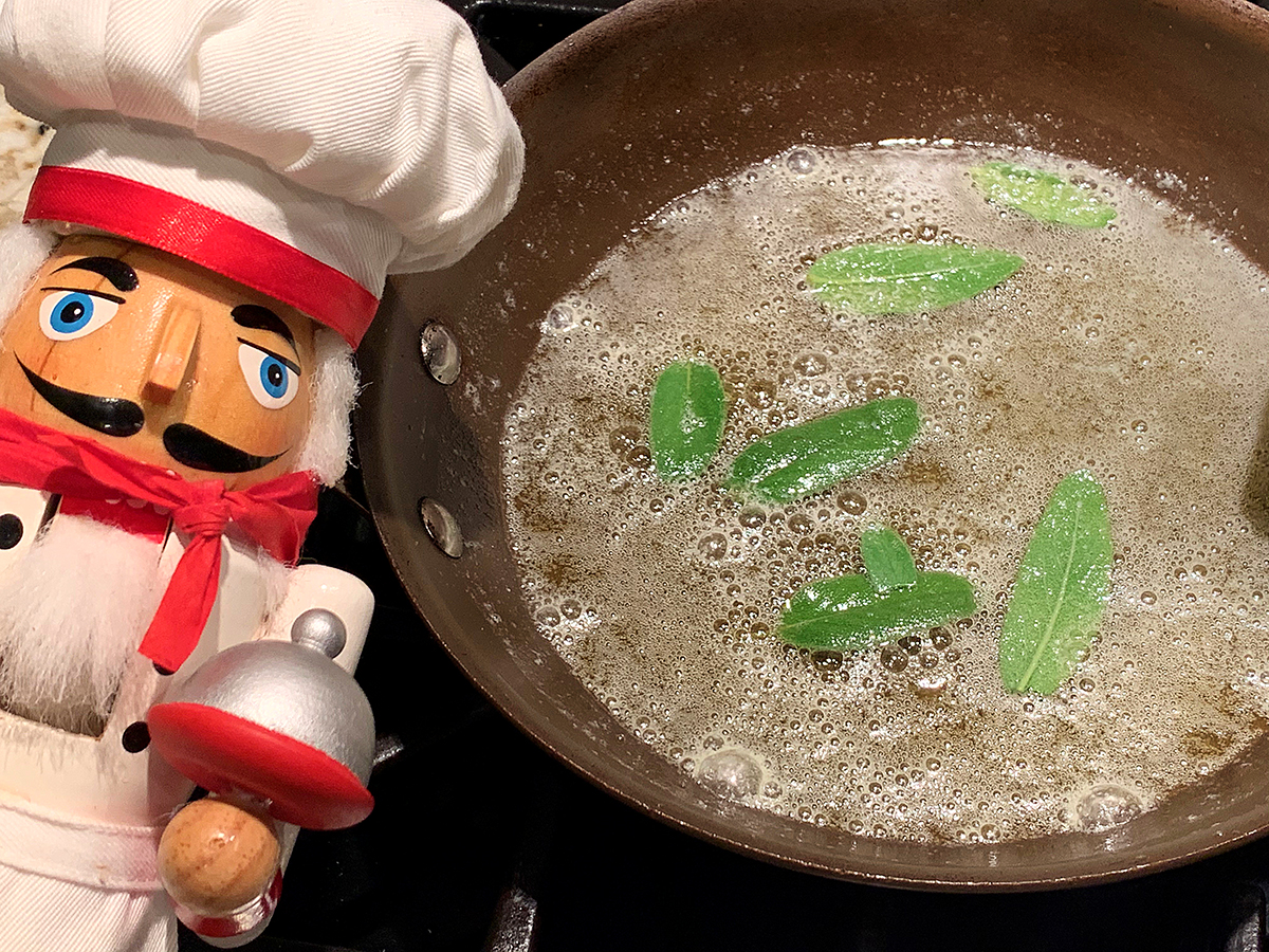 Fresh sage leaves in skillet with melted butter to make a sage brown butter.