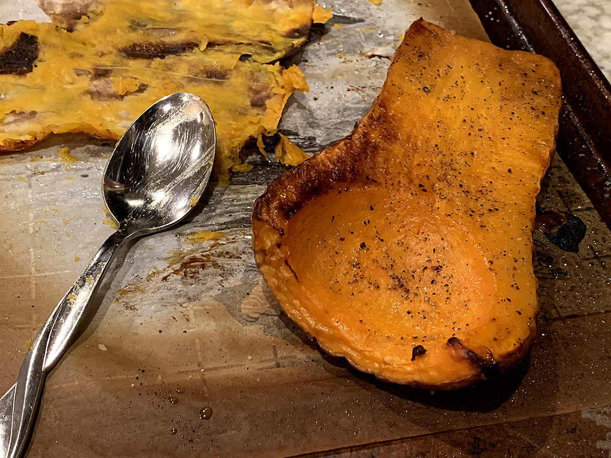 Roasted butternut squash halves with the flesh being scooped out.