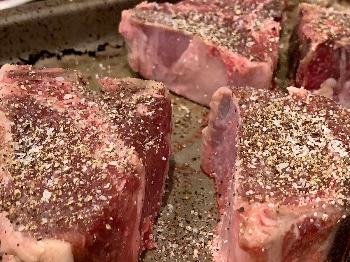 Close up of 3 heavily seasoned lamb loin chops.