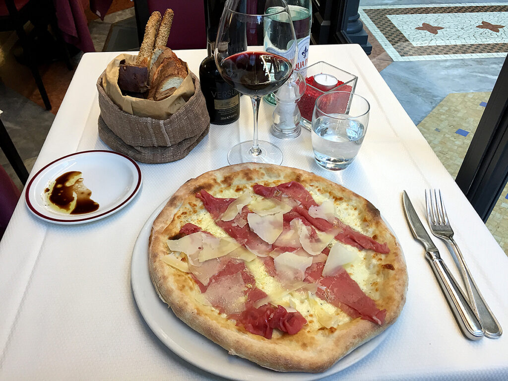 pizza on a white table with a glass of wine and a basket of bread sticks.