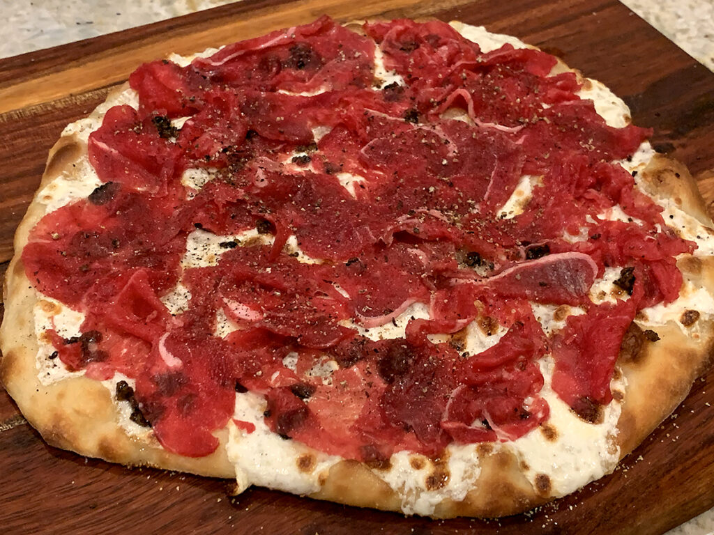 Thinly sliced pieces of raw filet mignon layered over the cheese and minced truffles on baked pizza dough.