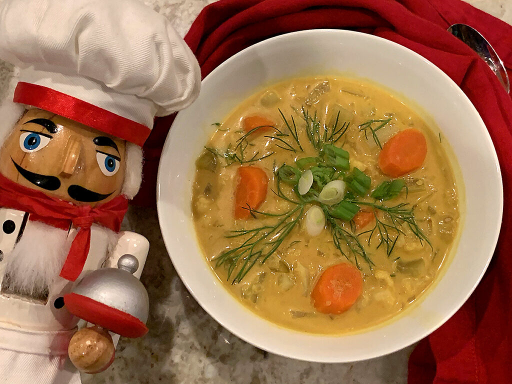 Pale yellow soup with Cauliflower, Fennel bulb and carrots in a round white bowl. Garnished with green onions, fennel fronds and chili oil. There's a nutcracker who looks like a chef in the foreground.