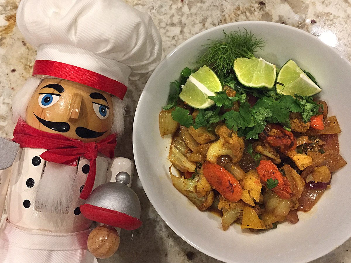 Cauliflower, fennel, carrots with lime wedges and fresh cilantro in a round white bowl. There's a nutcracker who looks like a chef in the foreground.