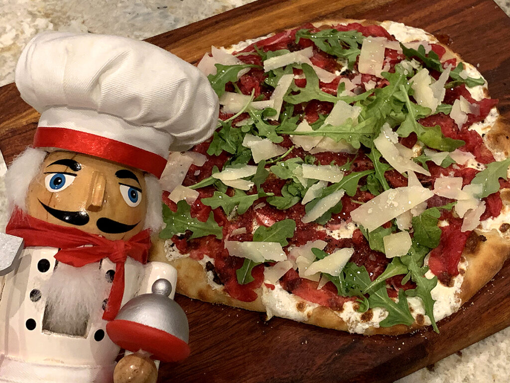 Beef carpaccio pizza with rare thin slices of beef, gooey cheese and arugula on a wood board. There's a nutcracker in the foreground who looks like a chef.
