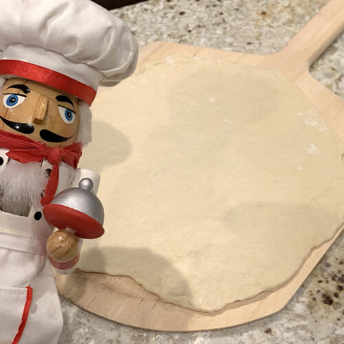Homemade rolled out pizza dough laying on a wood pizza peel. There's a nutcracker in the foreground who looks like a chef.