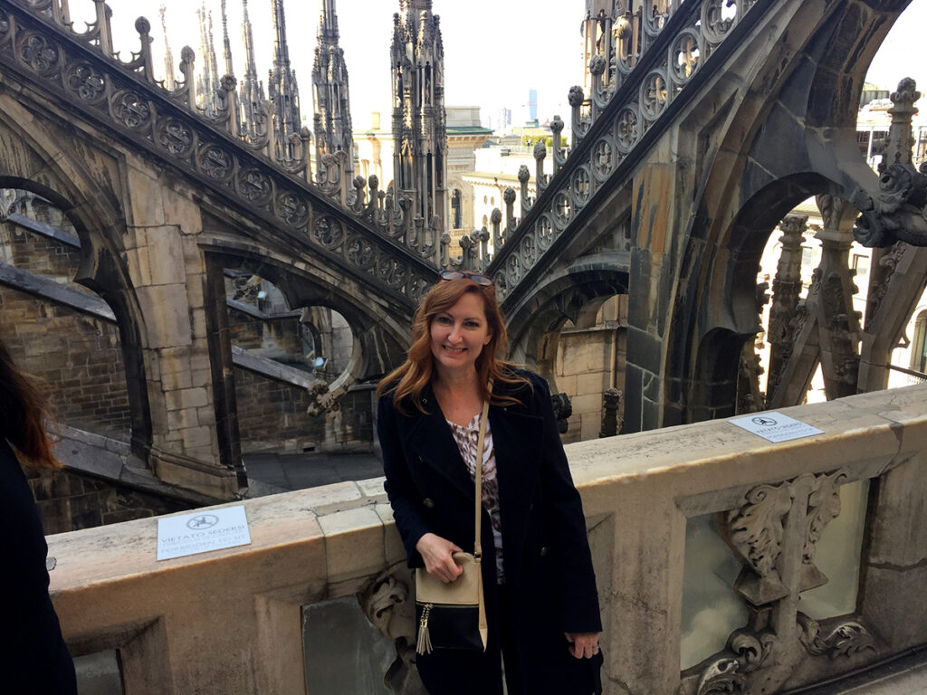 Caucasian woman with red hair standing amongst the flying buttresses of Cathedral Duomo.