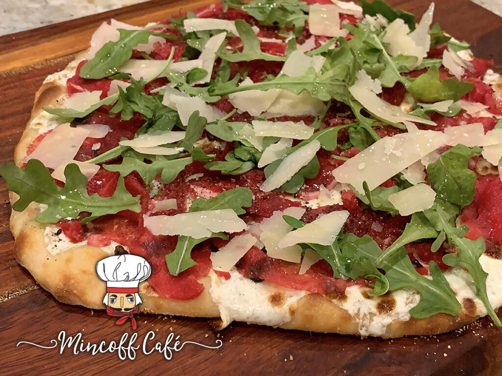 Beef carpaccio pizza with rare thin slices of beef, gooey cheese and arugula on a wood board.