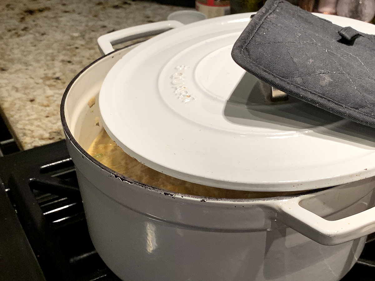 White dutch oven with lid partially closed and a square black pot holder on the handle.