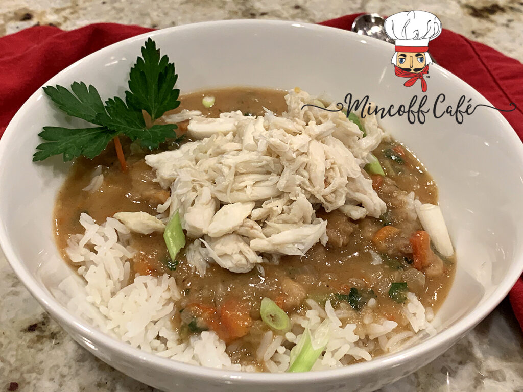 Reddish brown gravy with red and green vegetables on top of of a bit of white rice, topped with white crab meat. All in a round white bowl garnished with parsley and green onions.
