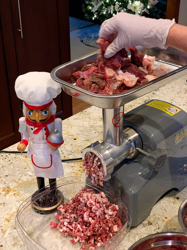 Venison and pork chunks in the tray of a meat grinder. Ground meat coming out the front. There's a nutcracker standing next to it that looks like a chef.
