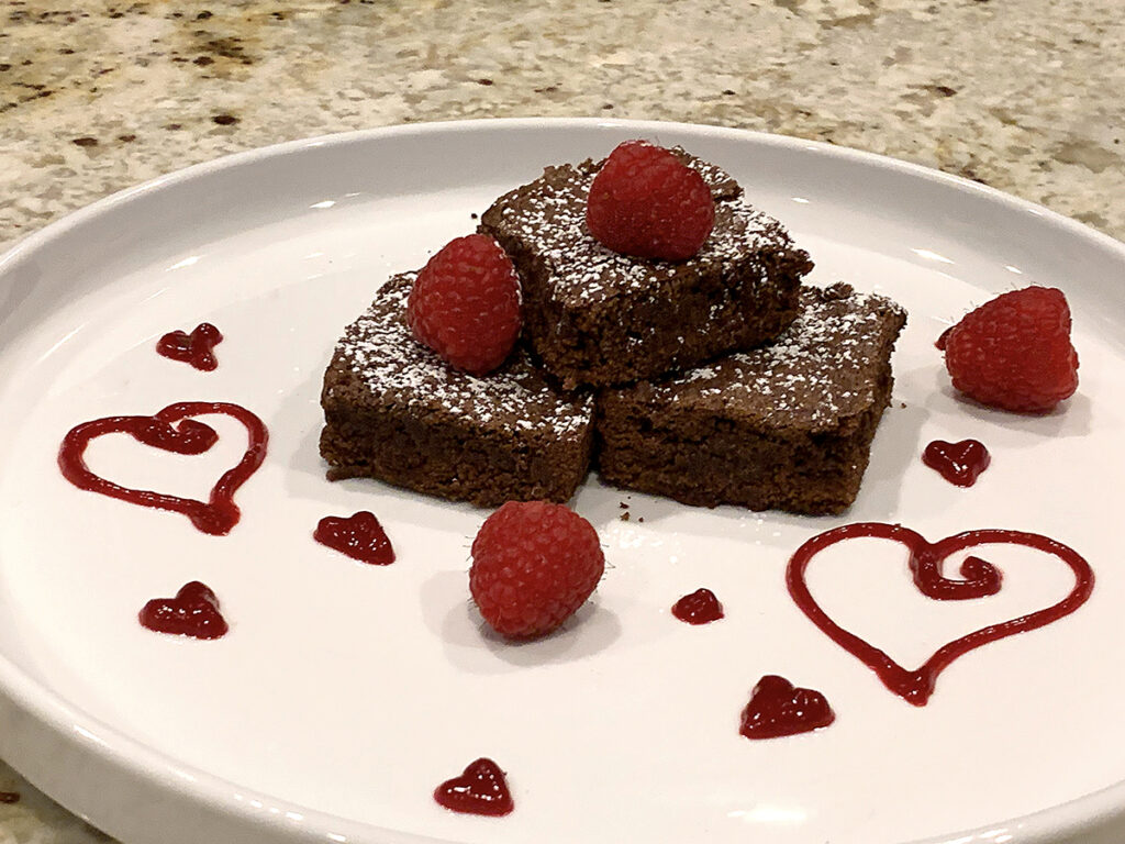 Three fudge brownies stacked on a white plate, dusted with powdered sugar and garnished with a hearts on the plate made with the red raspberry sauce as well as fresh raspberries.
