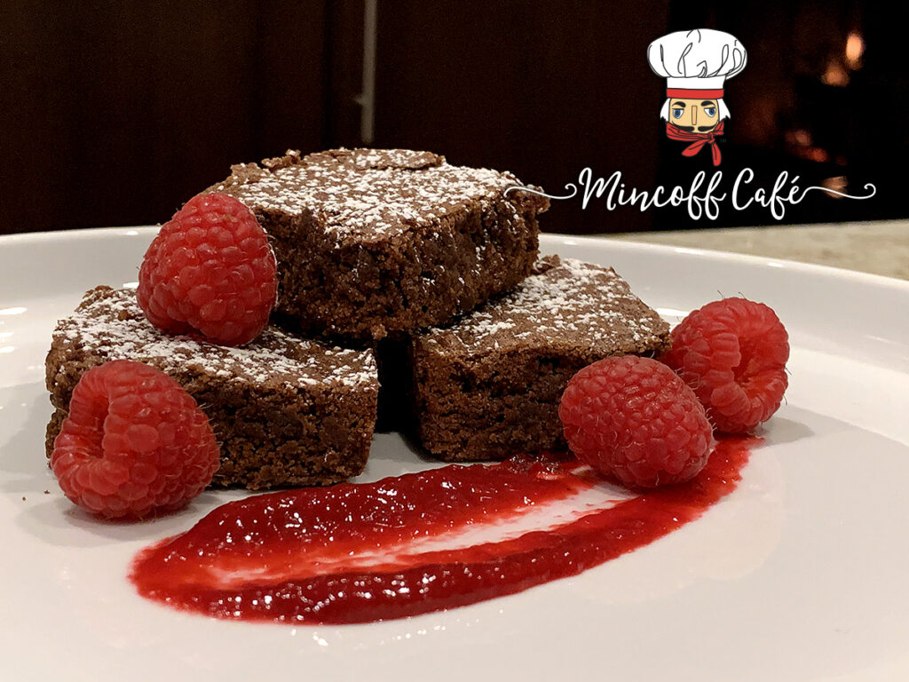 Three fudge brownies stacked on a white plate, dusted with powdered sugar and garnished with a swoosh of red raspberry sauce as well as fresh raspberries.
