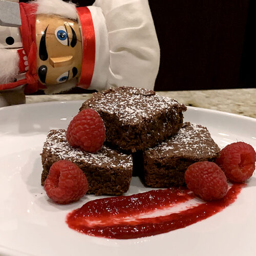 Three fudge brownies stacked on a white plate, dusted with powdered sugar and garnished with a swoosh of red raspberry sauce as well as fresh raspberries. There's also a nutcracker who looks like chef in the background.