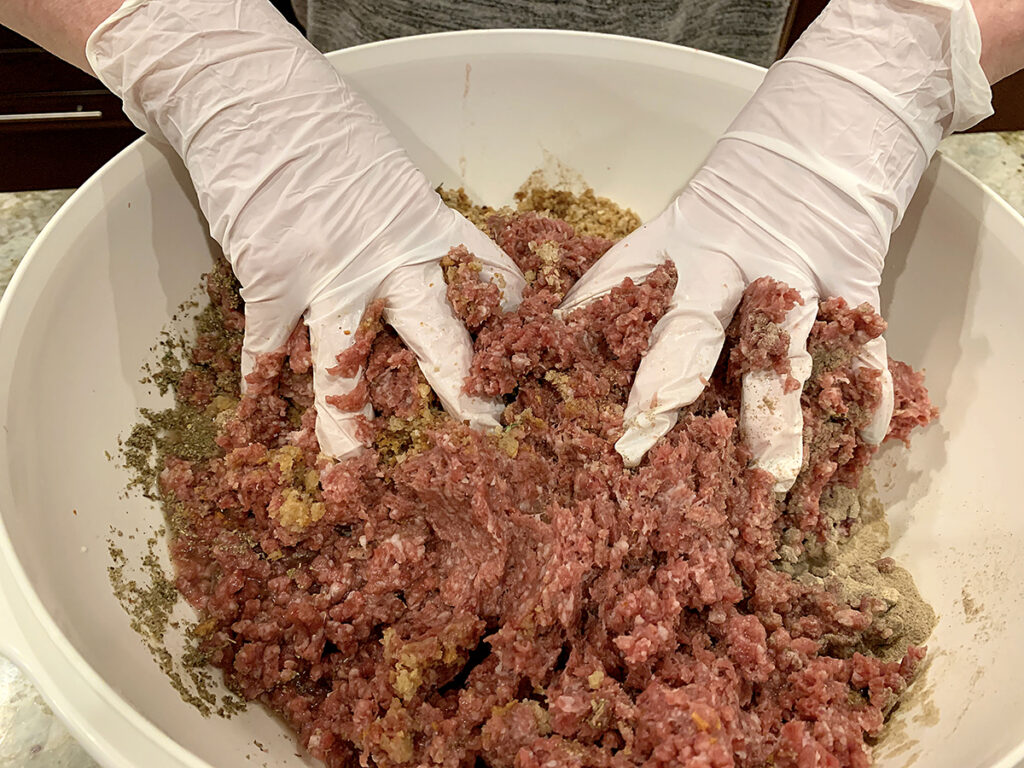 Two hands wearing white latex gloves mixing ground meat in a very large white plastic bowl.