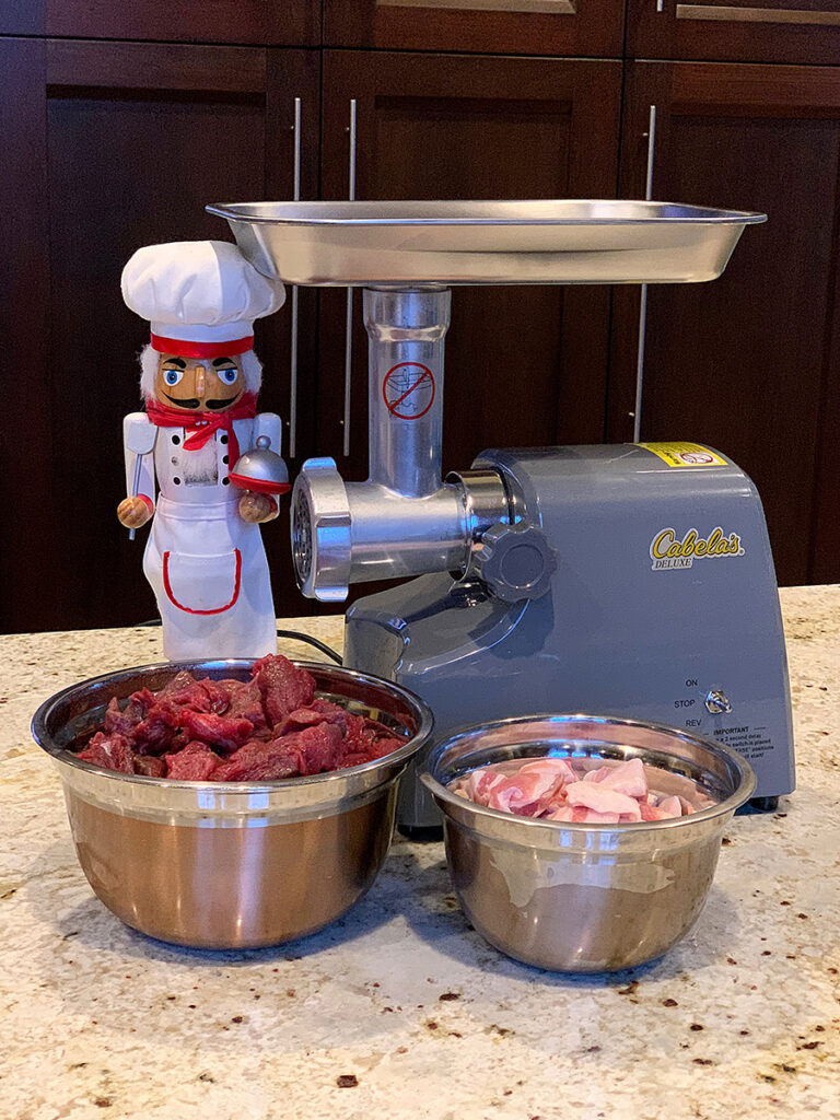 Grey meat grinder, with two bowls of meat in the foreground and a nutcracker who looks like a chef.