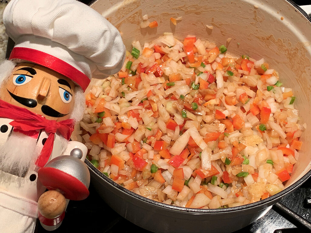 Chopped red bell pepper, onion, celery, jalapeno and minced garlic in a white dutch oven.  There's a nutcracker in the foreground who looks like a chef.