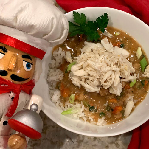 Reddish brown gravy with red and green vegetables on top of of a bit of white rice, topped with white crab meat. All in a round white bowl garnished with parsley and green onions. There's a nutcracker in the foreground who looks like a chef.