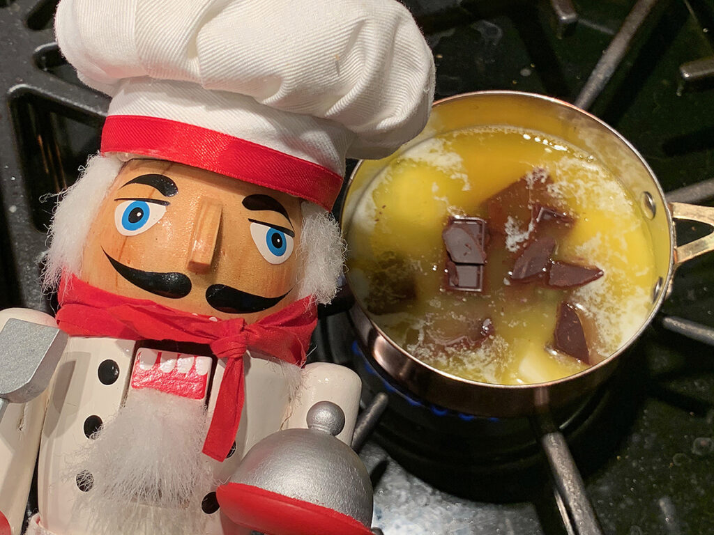 Chocolate and butter melting together in a small copper pan. There's a nutcracker who looks like a chef in the foreground.