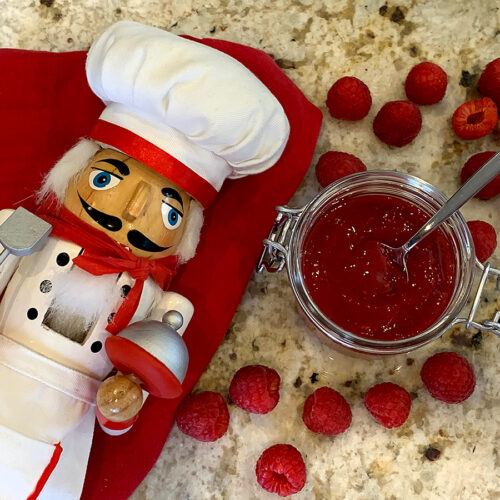 Overhead view of red seedless raspberry sauce in a clear glass jar surrounded by fresh raspberries. There's a nutcracker in the foreground who looks like a chef.