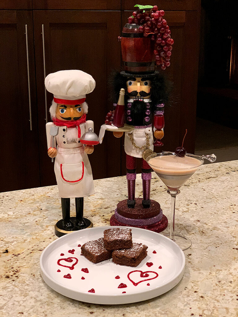 3 fudge brownies stacked on a white plate, garnished with hearts made from raspberry sauce. There's also a chocolate martini, one nutcracker who looks like a chef and another that looks like a somalia standing behind the plate.