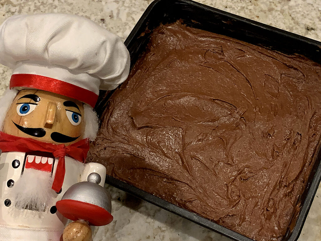 Dark brown batter in a square baking pan. There's a nutcracker in the foreground who looks like a chef.