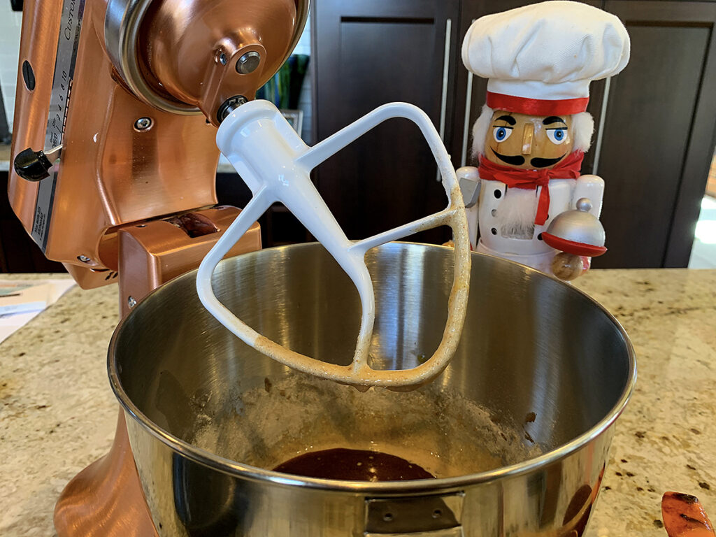 Mixing brownie batter in a large copper stand mixer, there's nutcracker who looks like a chef in the background.