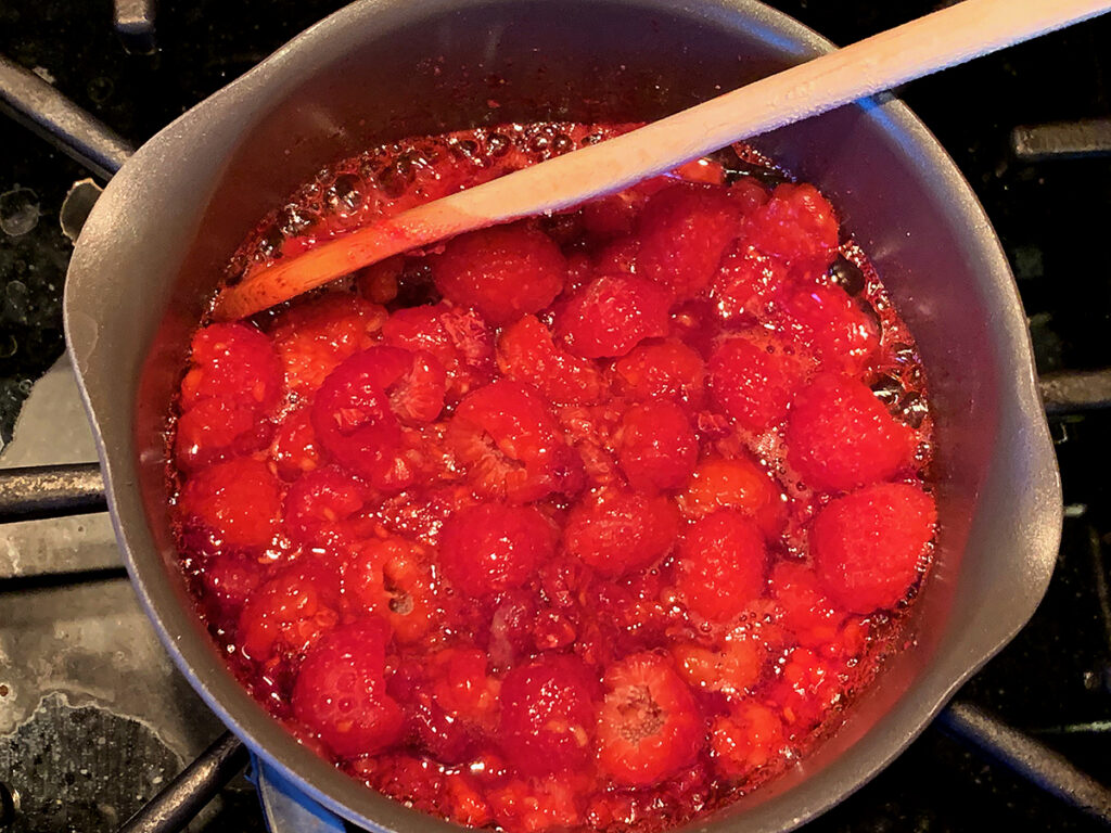Overhead view of raspberries simmering in a saucepan with a wooden spoon.