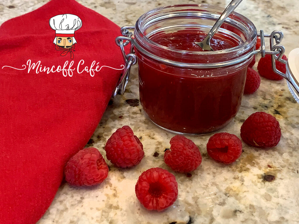 Red seedless raspberry sauce in a clear glass jar surrounded by fresh raspberries.