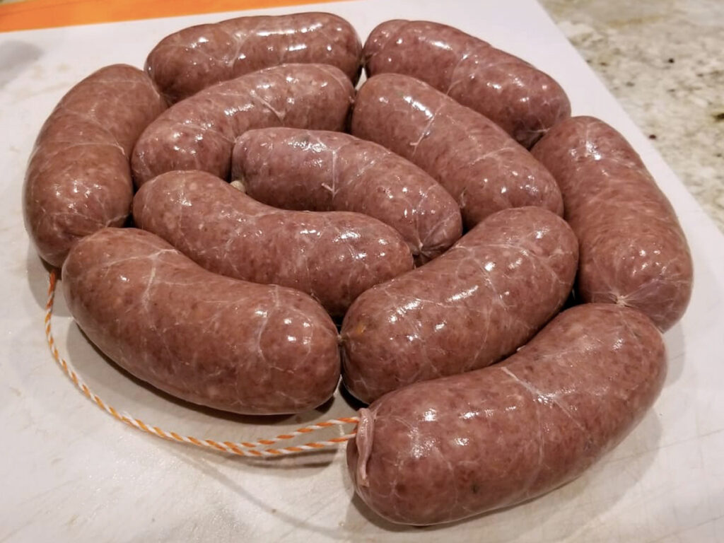 Coiled links of uncooked Homemade Venison British Bangers.