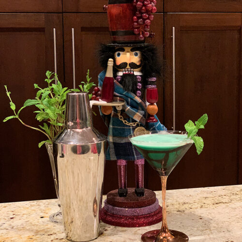 Green cocktail in a copper stemmed martini glass and garnished with mint leaves and chocolate drizzle. There's also silver a cocktail shaker, ice bucket and a nutcracker who looks like a sommelier.