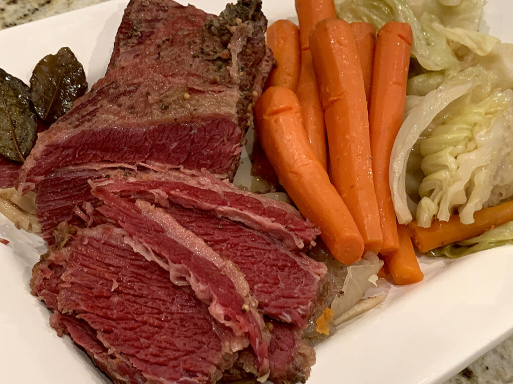 Large piece of corned beef partially sliced on a white platter with carrots and cabbage.