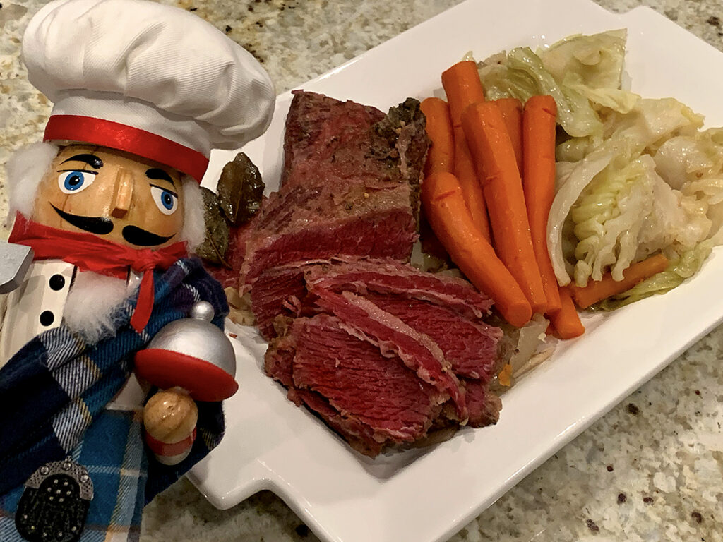A platter of corned beef, cabbage and carrots with a nutcracker who looks like a chef and is wearing a kilt in the foreground.