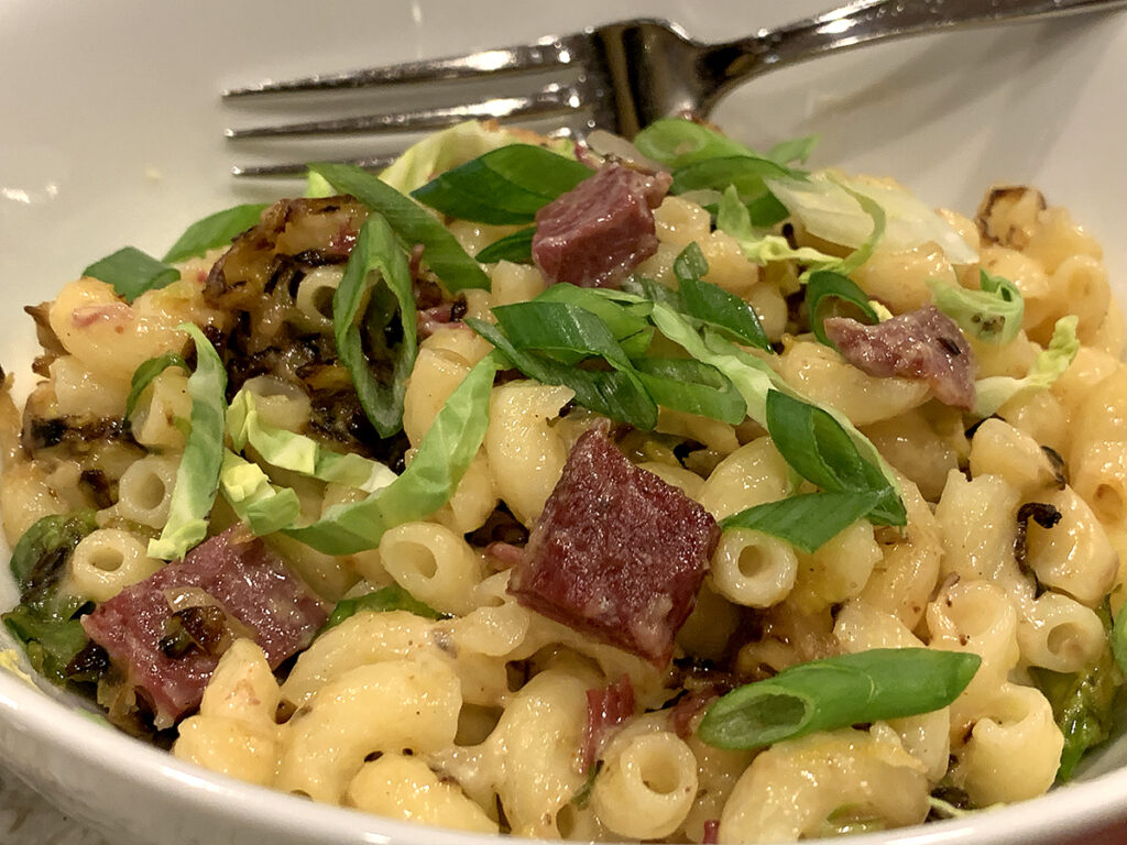 Elbow pasta with a pale cheese sauce, corned beef cubes, shredded brussels sprouts and garnished with chopped green onions.