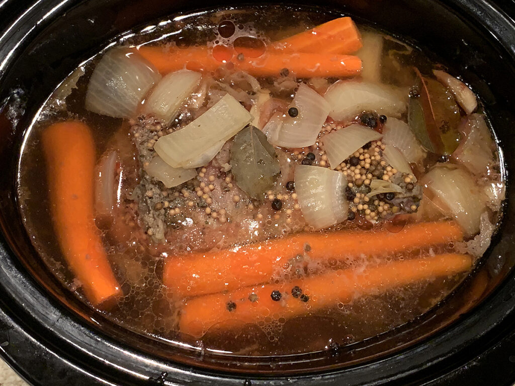 Corned beef, onions and carrots in a slow cooker.