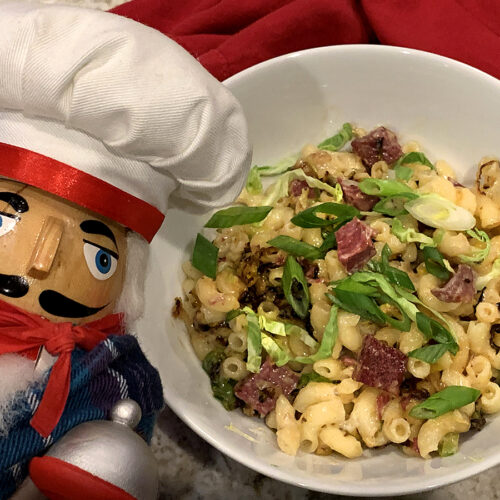 Mac and cheese with corned beef, sautéed brussles sprouts and garnished with sliced green onions, in a white bowl. There's a nutcracker in the foreground who looks like a chef.