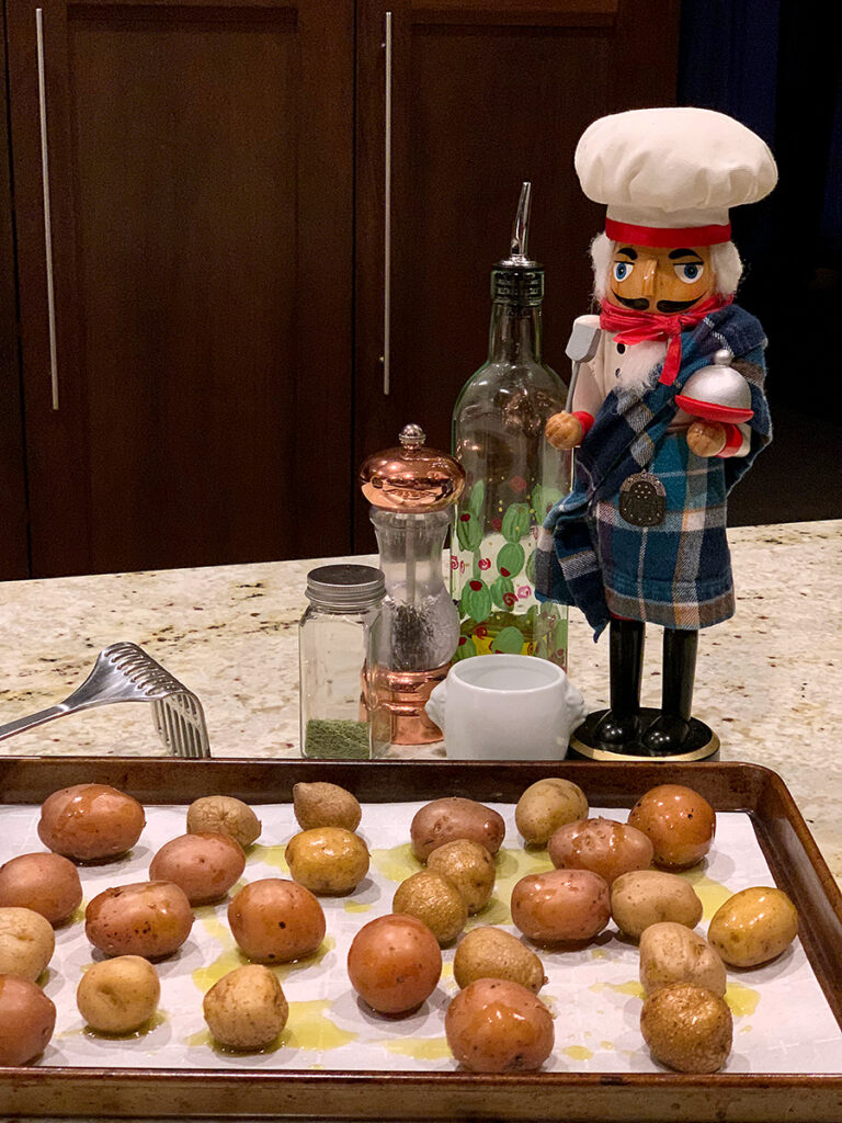 Sheet pan with single layer of baby potatoes ready for smashing. There's a nutcracker who looks like a chef and wearing a kilt in the background. There's also a bottle of olive oil, jar of dill weed, salt and pepper.
