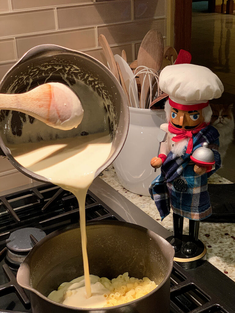 Pouring creamy pale cheese sauce onto cooked elbow pasta in a saucepan. There's a nutcracker standing by who looks like a chef.