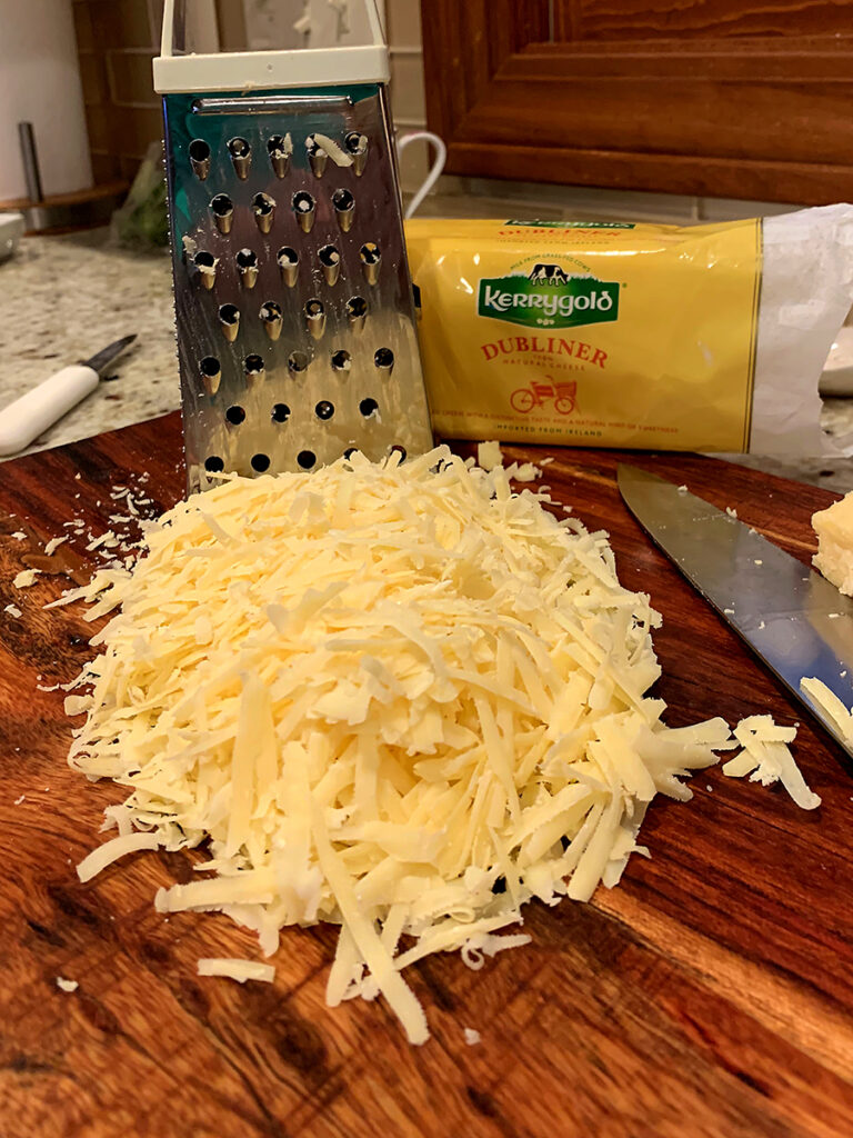 A pile of white Irish cheese that has just been shredded on a wood cutting board. there's box grater behind the pile of cheese.