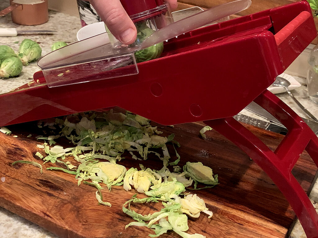 slicing brussels sprouts on a red mandoline with a safety guard.