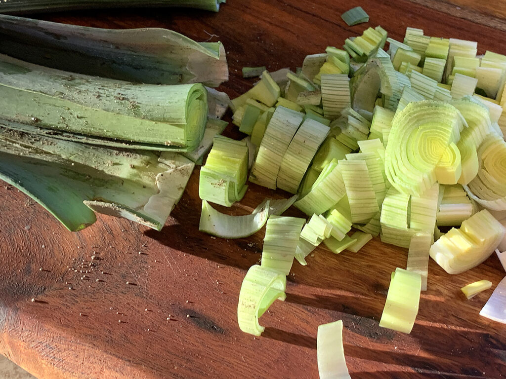 Two leeks cut vertically and then sliced horizontally on a wood board.