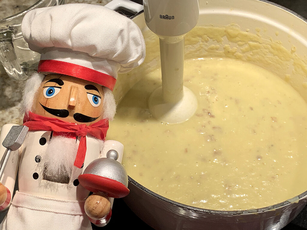 Pale and creamy yellow soup in a white dutch oven. It's being puréed with a stick blender and there's a nutcracker in the foreground who looks like a chef.
