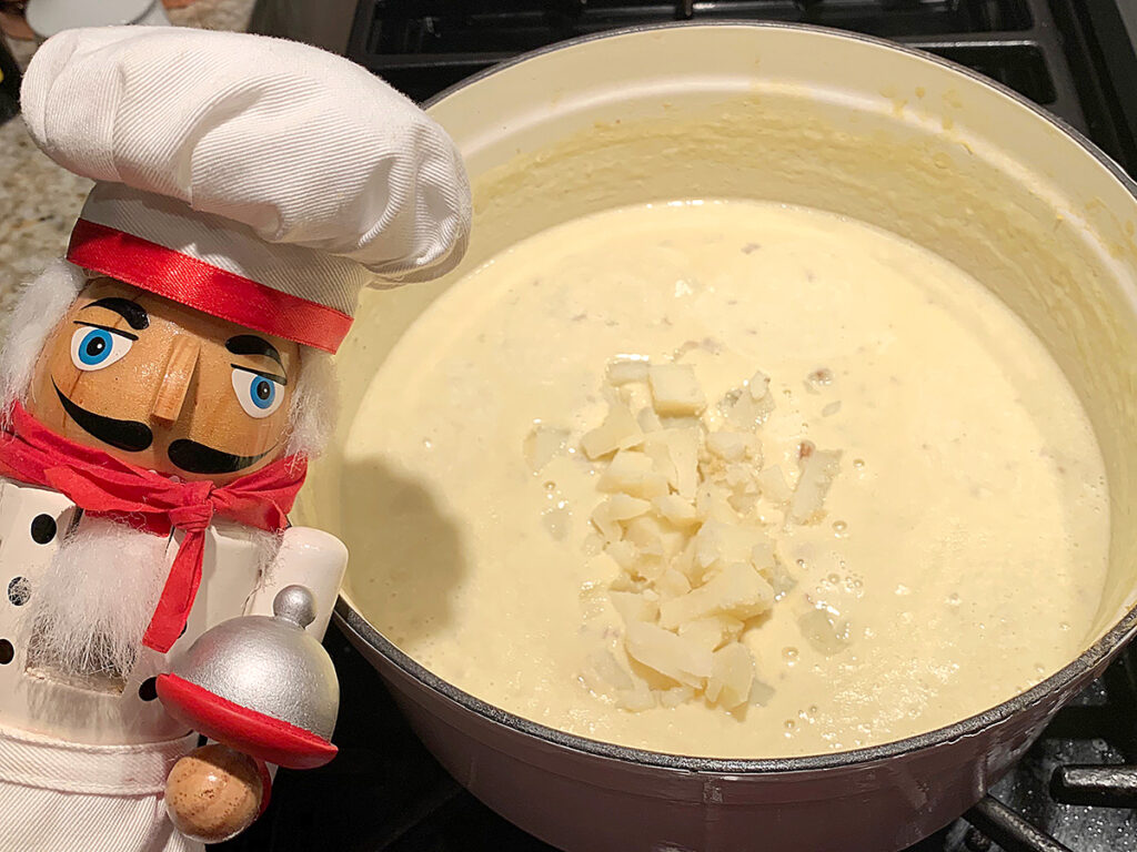 Creamy pale yellow soup in a white dutch oven. Chunks of baked potato have just been added to the pot, and there's a nutcracker in the foreground who looks like a chef.
